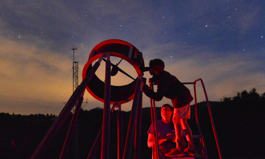 "25"" Optical telescope observing at night"